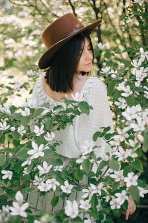 Sensual portrait of beautiful hipster woman in hat smelling  white flowers in spring. Stylish calm boho girl posing in blooming tree with flowers in sunny spring park. Copy space