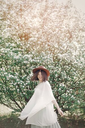 Happy boho woman in hat having fun in sunny light near white blooming tree in spring park. Stylish hipster girl enjoying spring and dancing. Atmospheric moment of happiness