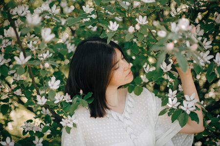 Stylish boho woman posing in white flowers in spring park. Hipster girl in boho outfit standing in white blooms of a tree. Calm portrait of beautiful brunette woman in spring