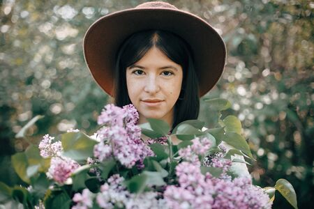 Sensual portrait of beautiful boho woman in hat holding lilac flowers bouquets in sunny spring park. Stylish calm hipster girl with purple lilac posing in spring garden. Copy space