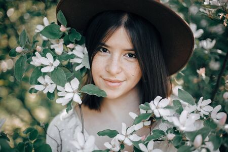Sensual portrait of beautiful hipster woman in hat smiling in white spring flowers. Stylish calm boho girl posing in blooming tree with flowers in sunny spring park. Copy space Zdjęcie Seryjne