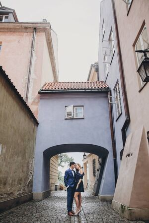 Stylish couple embracing together in european city street on background of old architecture. Fashionable man and woman in love enjoying day in city. Traveling together in Europe