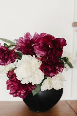 Stylish peony bouquet in black clay vase on rustic wooden background. White and pink peonies rural still life. Hello spring wallpaper. Happy Mothers day. Space text