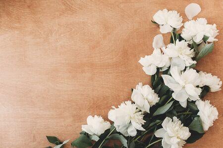 时髦的白色牡丹平躺在土气木桌上与文本的空间。贺卡样机。白色牡丹农村静物画。你好春天图像。母亲节快乐。国际妇女日