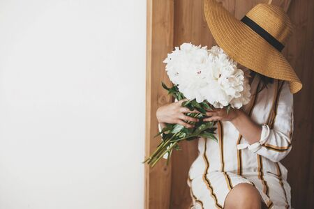 Stylish boho woman in hat holding white peony bouquet on rustic wooden background. Space for text. Hipster girl in dress posing with peonies. Happy Mothers day. International Womens days