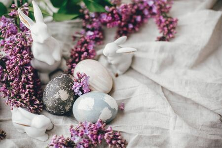 Modern Easter eggs, white bunnies and lilac flowers on linen rural fabric. Stylish holiday table decor. Happy Easter. Space for text. Natural dyed easter eggs and spring flowers.