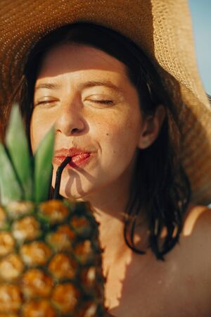 Beautiful young woman enjoying cocktail in pineapple, relaxing in pool on sunny summer vacation. Portrait of girl in hat with natural skin drinking cocktail on rooftop in luxury tropical resort