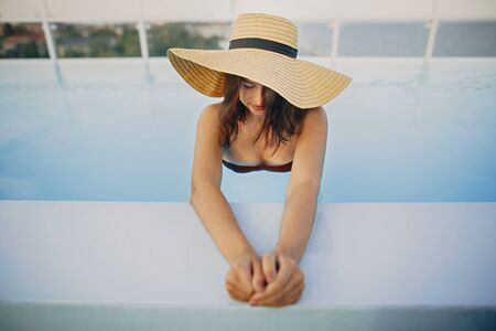 Stylish young woman in hat relaxing in blue pool and enjoying summer holiday. Summer tropical vacation. Girl in sunhat on vacation in luxury resort, swimming in pool on rooftop. Space for text