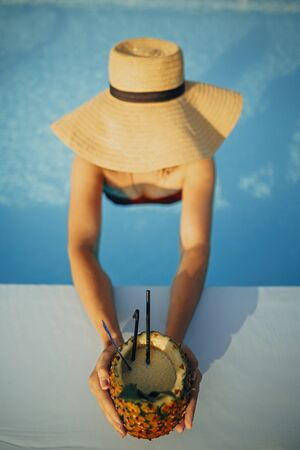 Beautiful young woman in hat holding delicious cocktail in pineapple and relaxing in pool, summer vacation. Girl enjoying warm sunshine in pool on rooftop in luxury tropical resort. Top view