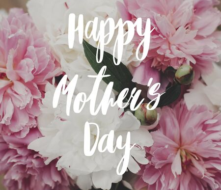 Happy Mothers Day text on peonies. Greeting card. Beautiful peony bouquet in sunny light. Stylish pink  and white peonies Stock fotó