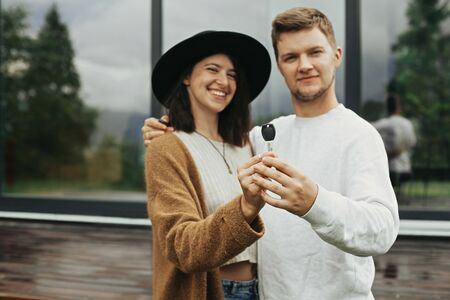 Home and family concept. Stylish hipster couple holding together key from their new home on background of terrace and big windows outdoors. Happy young family of homeowners, purchasing real estate