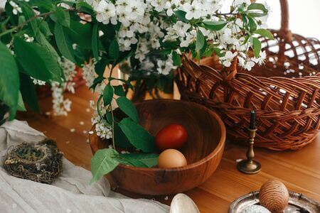 Easter Stylish Rural still life. Stylish Easter eggs with modern wax ornaments and natural dyed eggs on rustic wooden table with spring flowers, basket, candle, linen cloth, buxus.  Zero waste
