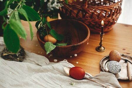 Easter Zero waste. Stylish Easter eggs with modern wax ornaments and natural dyed eggs on rustic wooden table with white spring flowers, basket, candle, linen cloth. Stylish Rural still life Reklamní fotografie