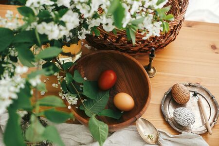 Happy Easter. Stylish Easter eggs with modern wax ornaments and natural dyed eggs on rustic wooden table with spring flowers, basket, candle, linen cloth, buxus. Stylish Rural still life. Zero waste Stock Photo