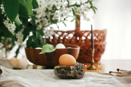 Natural Easter egg in rustic nest on background of candle, wicker basket, organic eggs, cherry flowers on wooden table. Happy Easter, atmospheric moment. Rural still life.  Zero waste