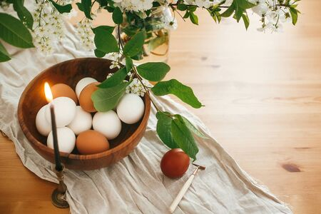 Rural Easter still life. Natural eggs in wooden bowl and vintage candle on linen fabric on background of cherry flowers and green leaves on rustic table. Happy Easter. Organic eggs