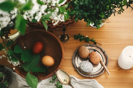 Happy Easter, Stylish Rural flat lay. Easter eggs with modern wax ornaments and natural dyed eggs on rustic wooden table with white spring flowers, buxus, spoon, candle, linen cloth. Zero waste