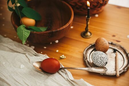 Easter Stylish Rural still life. Stylish Easter egg with modern wax ornaments and natural dyed eggs on rustic wooden table with spring flowers, basket, candle, linen cloth.  Zero waste