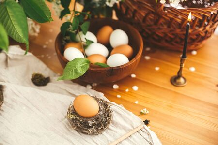 Happy Easter, atmospheric moment. Rural still life. Natural Easter egg in rustic nest on background of candle, wicker basket, organic eggs, cherry flowers on wooden table. Zero waste