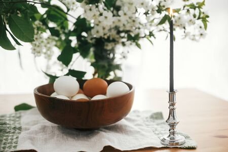 Natural Easter eggs in stylish wooden bowl and vintage candle on linen fabric on background of cherry flowers and green leaves. Happy Easter concept. Organic eggs, zero waste holiday