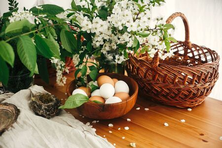 Natural Easter eggs, wicker basket, bird nest and cherry flowers on rustic table. Happy Easter, atmospheric moment. Rural still life. White and brown organic eggs. Zero waste
