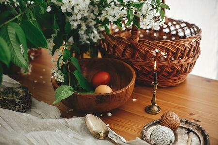 Modern Easter eggs with modern wax ornaments and natural dyed eggs on rustic wooden table with white spring flowers, basket, candle, linen cloth. Happy Easter. Stylish Rural still life. Zero waste