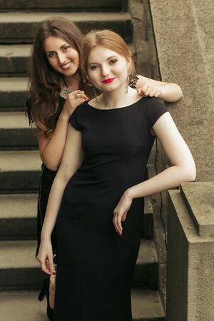 two luxury gorgeous woman  in black dress posing, standing on old stairs in city, classic gothic lady outfit