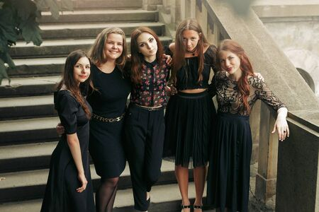 gorgeous luxury women in black dresses posing smiling on stairs under tree in the city. stylish lady party with gothic theme. elegant girls, view from top