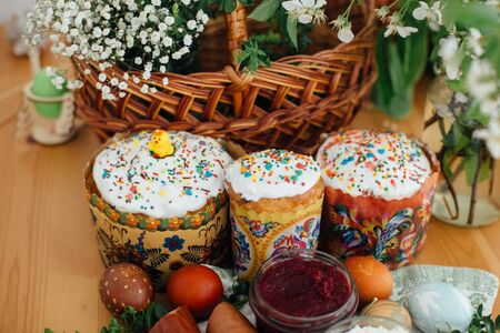 Easter homemade cakes, beets, eggs natural dyed, ham,  green branches and flowers on rustic wooden table with wicker basket. Traditional Easter Food for blessing in church