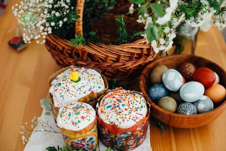 Easter cake, easter eggs natural dyed, candle, green branches and flowers on rustic wooden table with wicker basket. Traditional Easter Food for sanctify in church