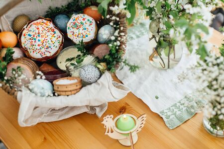 Traditional Easter basket for blessings in church. Easter modern eggs, cake, ham, beets, butter in rustic basket decorated with green buxus branches and flowers on wooden table with candle Standard-Bild