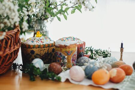 Traditional Easter food on rustic table. Homemade easter cake, easter eggs natural dyed, candle, green branches and flowers with wicker basket on wooden background. Easter Food for sanctify