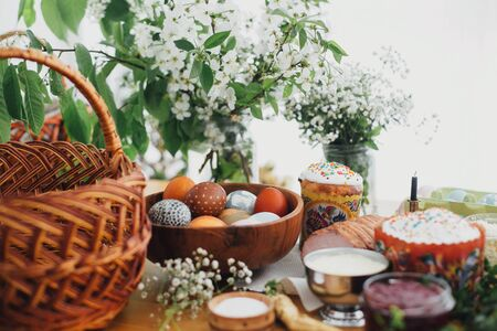 Easter eggs natural dyed, easter bread, ham, beets, butter, green branches and flowers on rustic wooden table with wicker basket and candle. Traditional Easter Food for blessing in church Stock Photo