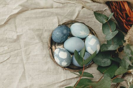 Happy Easter. Modern Easter eggs on vintage plate on rustic table with spring flowers and eucalyptus. Stylish pastel blue Easter eggs painted in natural dye from red cabbage. Rural still life