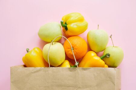 Fruits and vegetables in paper bag on pink background flat lay. Zero waste shopping, plastic free. Shopping groceries online. Order fresh organic food and get them delivered safe.