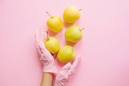 Hands in pink glove holding apples on pink background flat lay. Safe shopping in quarantine. Order food online with delivery and stay home. Prevention of virus epidemic. Stay safe. Banque d'images