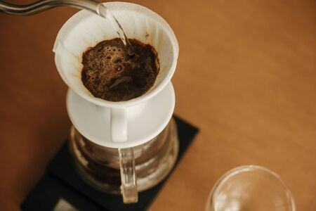 Alternative coffee brewing v60 closeup. Barista making filter coffee on brown background. Pouring hot water from steel kettle in filter with ground coffee in pour over on scale.