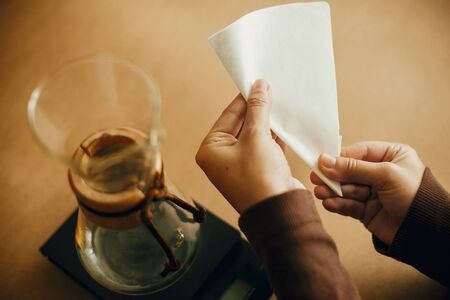 Preparing for alternative coffee brewing v60. Fold coffee filter. Hands folding paper filter for pour over and glass kettle on scale on brown background. Imagens