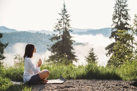 Young woman practicing yoga and sitting in lotus position on top of mountain among grass in sunny morning light.