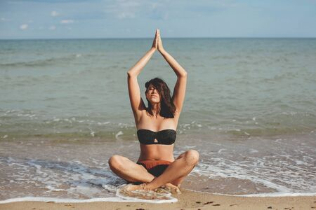 Yoga and meditation on beach. Young beautiful woman practicing yoga, sitting on seashore and meditaning. Mental health and self care concept. Summer vacation