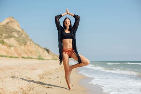 Young beautiful woman practicing yoga on the beach, standing in tree pose and meditaning at sea. Mental health and self care. Happy girl relaxing on seashore on summer vacation 스톡 콘텐츠