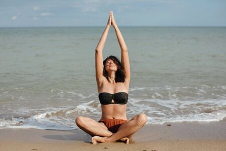 Young beautiful woman practicing yoga on the beach, sitting on sand and meditaning. Mental health and self care concept. Happy girl relaxing on seashore on summer vacation
