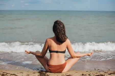 Mental health and self care concept. Young fit woman practicing yoga on the beach, sitting on sand and looking at sea waves. Girl meditating on summer vacation. 스톡 콘텐츠