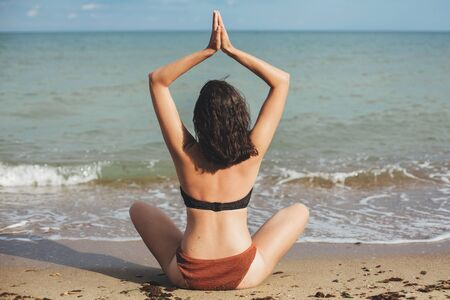 Young fit woman practicing yoga on the beach, sitting on sand and looking at sea waves. Girl meditating on summer vacation. Mental health and self care concept 스톡 콘텐츠