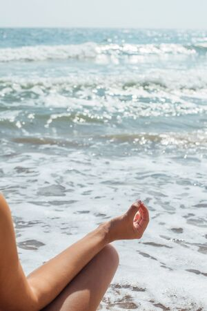 Closeup of woman hand in lotus position on background of sunny waves while practicing yoga and meditating. Yoga and meditation on beach at sea. Mental health and self care 스톡 콘텐츠