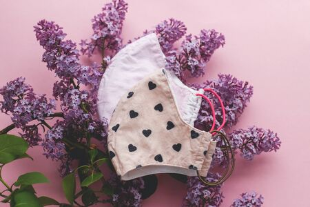 Zero waste lifestyle during coronavirus outbreak. Reusable face masks with lilac flowers on pink background flat lay.  Handmade textile face mask. Choose reusable textile face mask