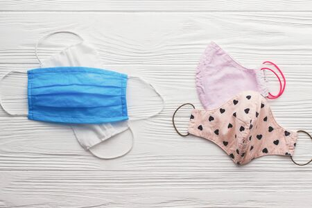 Reusable face masks and single use medical masks on white wooden background flat lay. Zero waste lifestyle during virus outbreak. Disposable mask and handmade textile mask 스톡 콘텐츠