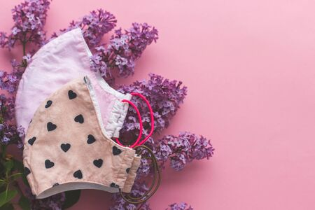 Choose reusable textile face mask. Reusable face mask with lilac flowers on pink background flat lay. Handmade textile face mask. Zero waste lifestyle during coronavirus outbreak