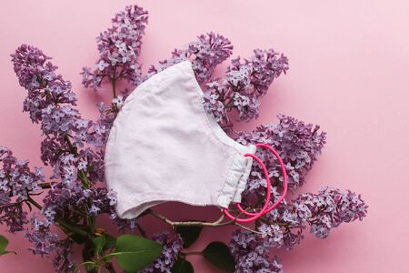 Reusable face mask with lilac flowers on pink background flat lay. Zero waste lifestyle during virus outbreak. Handmade textile face mask. Choose reusable textile face mask