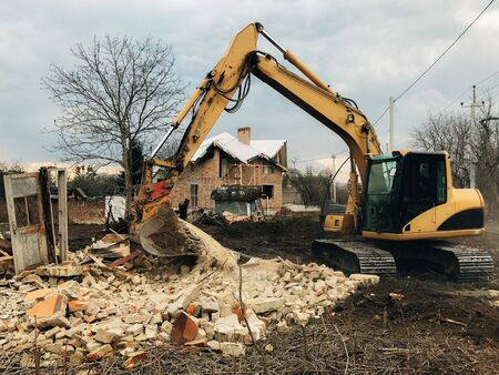 Bulldozer clearing land from old bricks and concrete from walls with dirt and trash. Backhoe machinery ruining house. Excavator destroying brick house on land in countryside. 스톡 콘텐츠 - 147203307